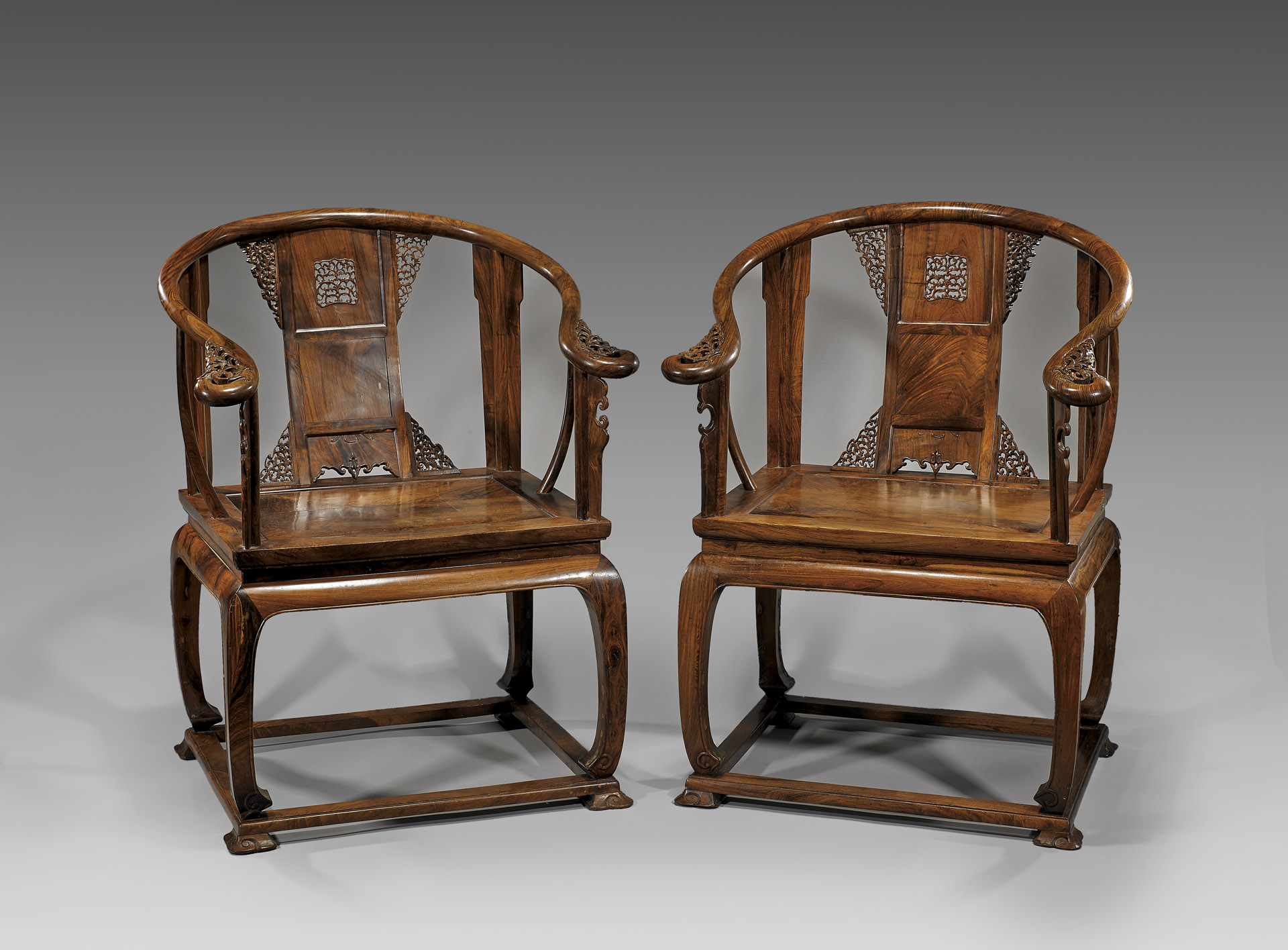 This Antique Pair Of Chinese Carved Huanghuali Wood Armchairs With Intricately Backsplat And Curvilinear Arms