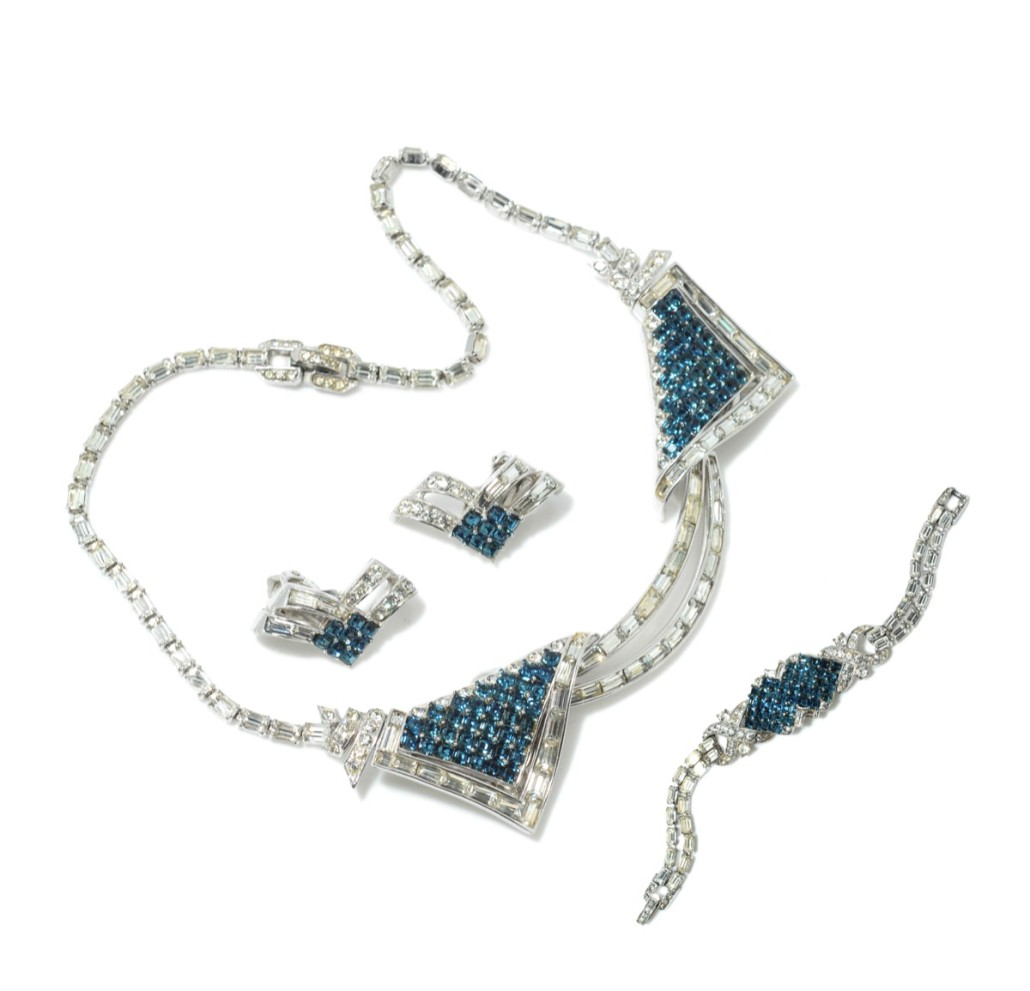 This rare parure comprising earrings, bracelet and necklace dates from the 1940s and was designed by Marcel Boucher (1898-1965). The necklace also contains a pin that can be released and worn separately to secure a fur stole. The stones simulate light blue sapphires and diamonds on silver tone metal, which is rhodium plated. Boucher was apprenticed to Pierre Cartier and moved to New York from his native France in the 1920s, working for Mazer Brothers. He set up on his own in 1937. His wife Sandra, who had worked for the Fifth Avenue jeweler Harry Winston, continued the business after her husband's death. Photo Candice Horley